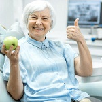 elderly woman holding a green apple and giving a thumbs up
